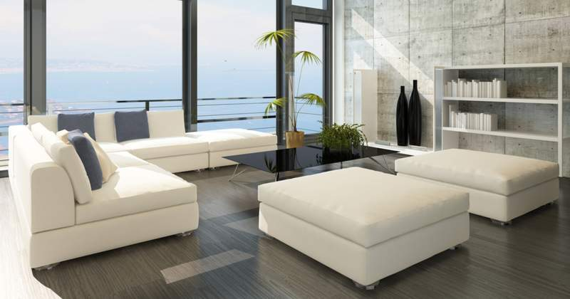 Modern living room with white furniture and a top-bottom window view of the ocean from high up