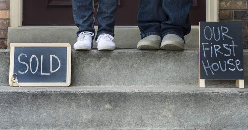 Photo with signs 'Sold' and 'Our First House' with two people (their legs and shoes only) standing on doorsteps in entrance